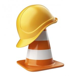 Orange traffic cone with yellow hard hat on top